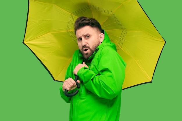 Hübscher bärtiger junger mann, der regenschirm auf weiß isoliert hält