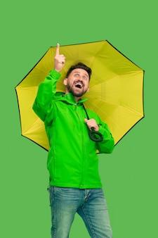 Hübscher bärtiger junger mann, der regenschirm hält