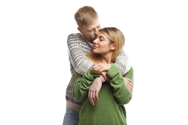 Hübscher bärtiger junger mann, der seine süße freundin umarmt und sie auf die stirn küsst und seine liebe und zärtlichkeit ausdrückt. schönes paar, das nach langer trennung kuschelt und die augen geschlossen hält