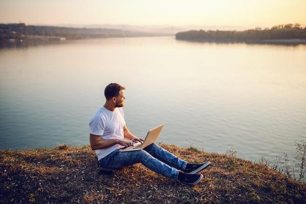 Hübscher bärtiger kaukasischer blonder mann, der auf klippe sitzt