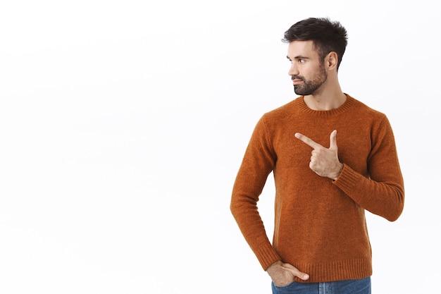 Hübscher bärtiger kaukasischer mann dreht das gesicht nach links, schaut und zeigt auf leerzeichen, um ein gutes geschäft auszuchecken, ein interessantes angebot oder eine rabattaktion gefunden, weiße wand stehen