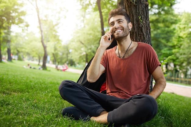 Hübscher bärtiger kerl, der im park auf gras ruht, auf handy spricht und glücklich lächelt