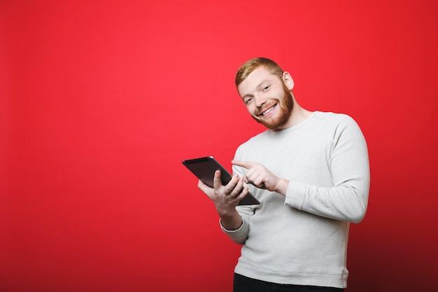 Hübscher bärtiger kerl, der lächelt und kamera betrachtet, während er auf lebendigem rotem hintergrund steht und tablette verwendet