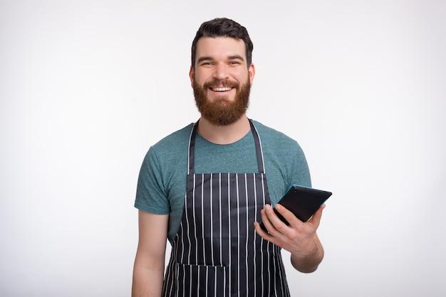 Hübscher bärtiger kocher, der schürze trägt, hält seine tablette, während er auf weißer wand lächelt