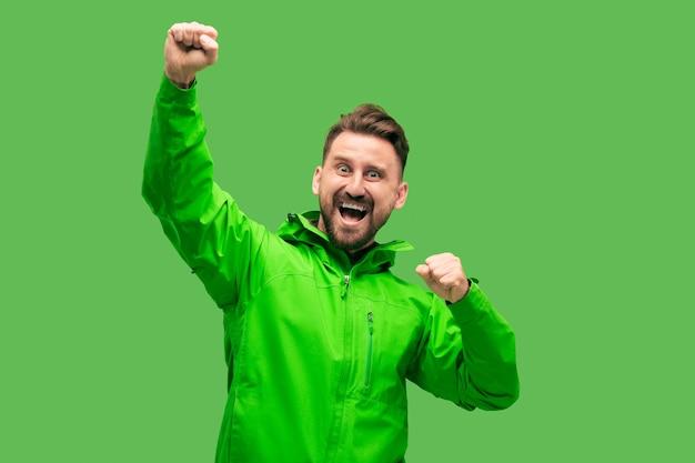 Hübscher bärtiger lächelnder glücklicher junger mann, der front lokalisiert auf lebendigem trendigem grünem studio betrachtet
