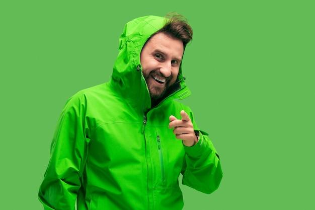 Hübscher bärtiger lächelnder glücklicher junger mann, der kamera lokalisiert auf lebendigem trendigem grünem studio betrachtet. konzept des herbstes und der kalten zeit. konzepte menschlicher emotionen