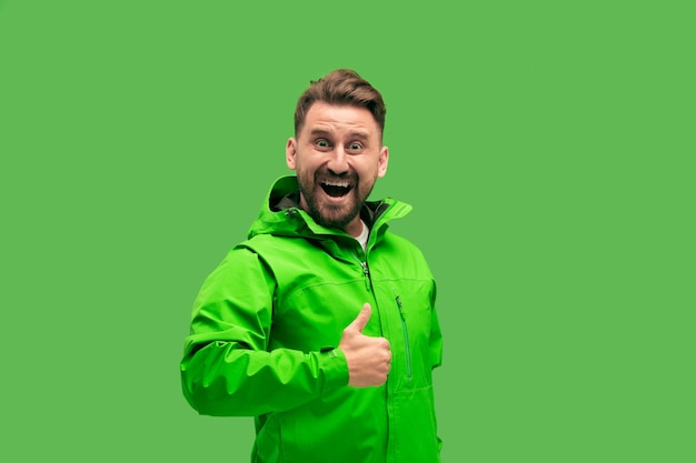 Hübscher bärtiger lächelnder glücklicher junger mann, der kamera lokalisiert auf lebendigem trendigem grünem studio betrachtet.