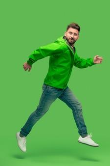 Hübscher bärtiger lächelnder glücklicher junger mann, der lokal auf lebendigem trendigem grünem studio läuft.