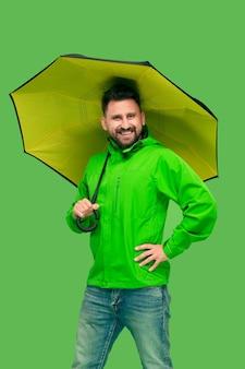 Hübscher bärtiger lächelnder glücklicher junger mann, der regenschirm hält und front lokalisiert auf lebendigem trendigem grünem studio betrachtet
