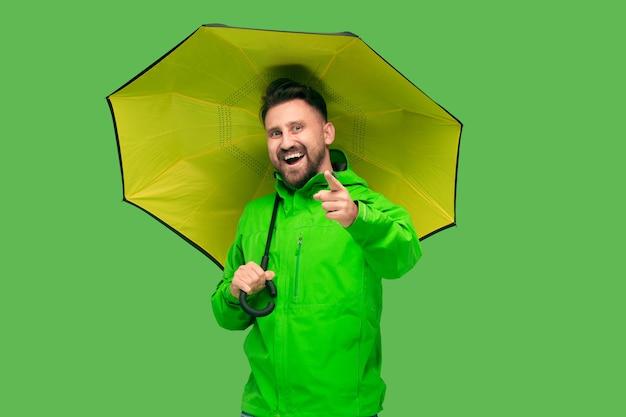 Hübscher bärtiger lächelnder glücklicher junger mann, der regenschirm hält und kamera lokalisiert auf lebendigem trendigem grünem studio betrachtet. konzept des beginns von herbst und kälte