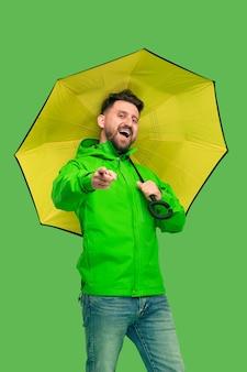 Hübscher bärtiger lächelnder glücklicher junger mann, der regenschirm hält und kamera lokalisiert auf lebendigem trendigem grünem studio betrachtet.