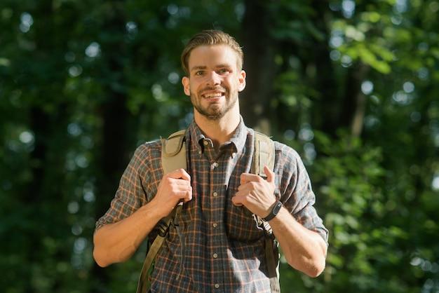 Hübscher bärtiger männlicher rucksacktourist mit rucksack auf seinen schultern. attraktiver tourist mit rucksack. alleinreisender tourist in der naturlandschaft. touristische kampagne.