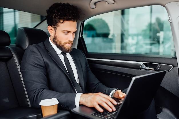 Hübscher bärtiger manager, der an seinem laptop mit kaffee arbeitet, um auf den rücksitz des neuen autos zu gehen