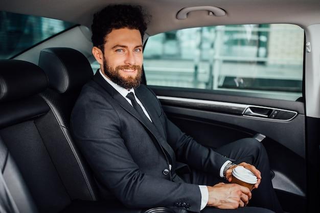 Hübscher bärtiger manager, der mit kaffee sitzt, um auf dem rücksitz des neuen autos zu gehen