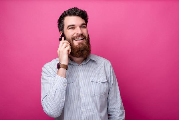 Hübscher bärtiger mann, der am telefon auf rosa hintergrund mit kopienraum spricht.