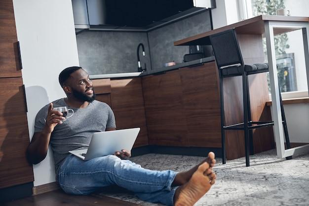 Hübscher bärtiger mann, der auf dem boden sitzt und den laptop auf den knien hält, während er auf das fenster schaut