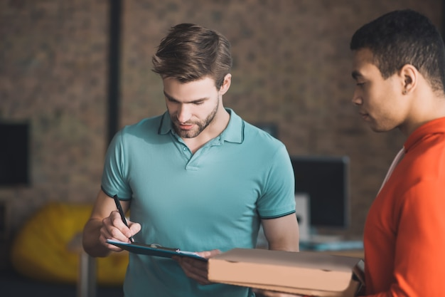Hübscher bärtiger mann, der die rechnung betrachtet, während prüfend, wo sie zu unterzeichnen ist