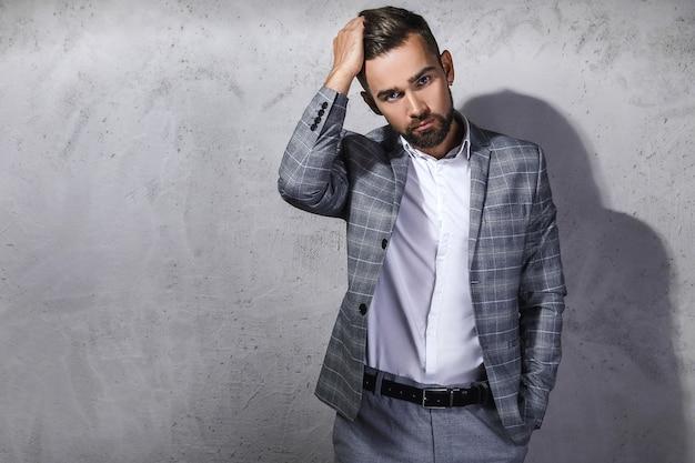Hübscher bärtiger mann, der grauen karierten anzug trägt, wirft gegen betonwand auf