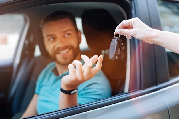 Hübscher bärtiger mann, der in seinem auto sitzt und autoschlüssel erhält, die von einer zarten weiblichen hand übergeben werden