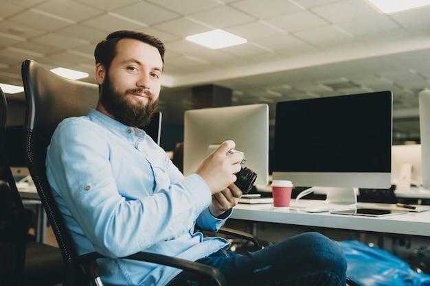 Hübscher bärtiger mann, der kamera hält und lächelt, während er am schreibtisch im büro sitzt