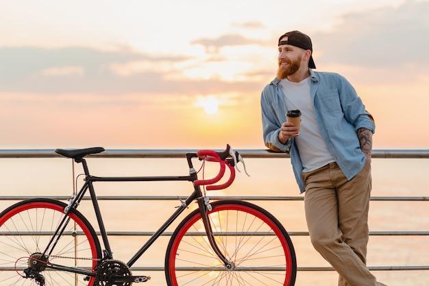 Hübscher bärtiger mann, der mit dem fahrrad im morgensonnenaufgang durch das meer reist, das kaffee trinkt, gesunder reisender des aktiven lebensstils