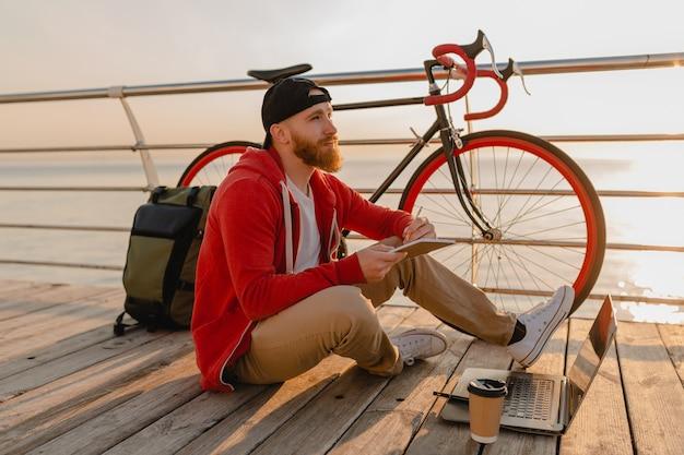 Hübscher bärtiger mann des hipster-stils, der online-freiberufler auf laptop mit rucksack und fahrrad im morgensonnenaufgang durch den gesunden aktiven lebensstilreisenden-rucksacktouristen des meeres arbeitet