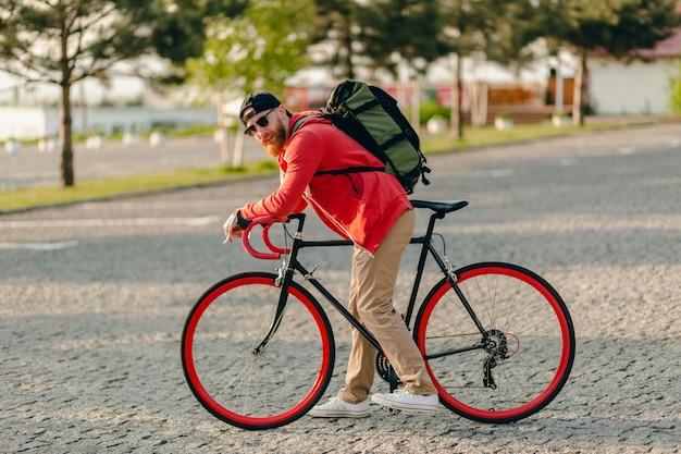 Hübscher bärtiger mann des hipster-stils im roten kapuzenpulli und in der sonnenbrille, die allein mit rucksack auf fahrradreisenden rucksacktouristen des gesunden aktiven lebensstils reiten Kostenlose Fotos