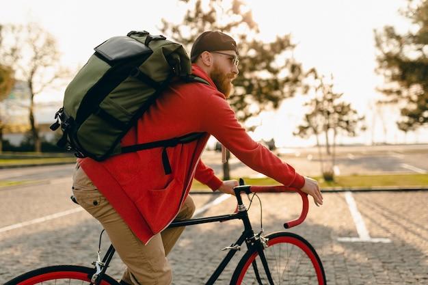 Hübscher bärtiger mann des hipster-stils im roten kapuzenpulli und in der sonnenbrille, die allein mit rucksack auf fahrradreisenden rucksacktouristen des gesunden aktiven lebensstils reiten