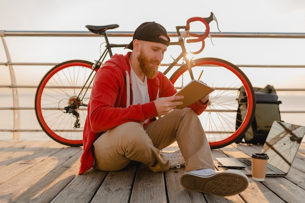 Hübscher bärtiger mann im hipster-stil, der online-freiberufler studiert, der notizen mit rucksack und fahrrad im morgensonnenaufgang durch das meer macht gesunder aktiver lebensstil reisender rucksacktourist