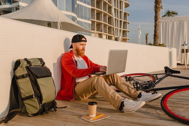 Hübscher bärtiger mann im hipster-stil, der online freiberuflich auf laptop mit rucksack und fahrrad-aktivem lebensstilreisenden-rucksacktouristen arbeitet