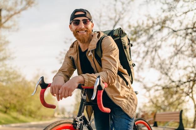 Hübscher bärtiger mann im hipster-stil in jacke und sonnenbrille, die allein mit rucksack auf fahrrad-rucksacktourist für gesunden aktiven lebensstil reiten