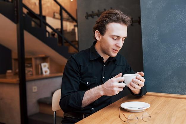Hübscher bärtiger mann im karierten hemd, das gabel hält, das im café isst und lächelt.