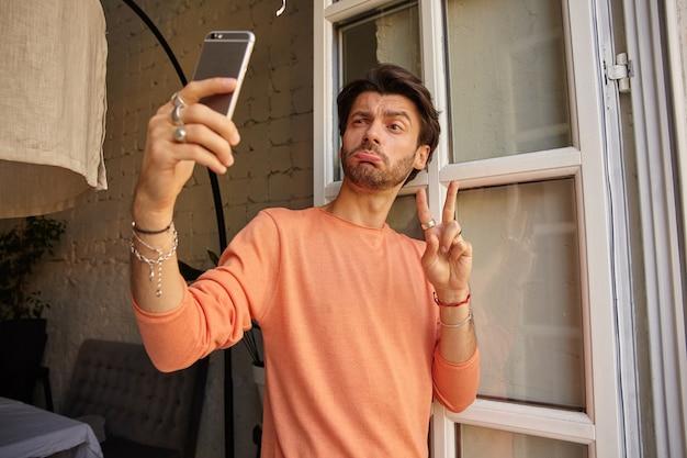Hübscher bärtiger mann im pfirsichfarbenen pullover, der selfie mit seinem smartphone macht, lustige gesichter macht und zwei finger in friedensgeste hebt