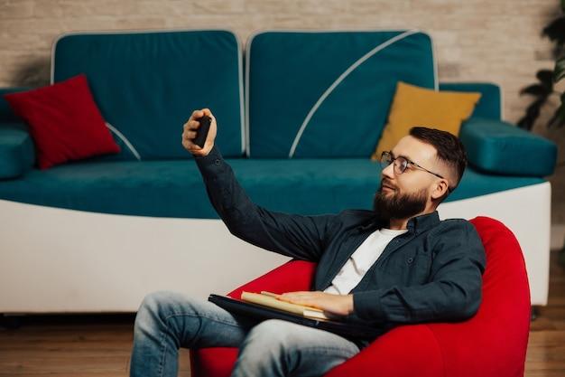 Hübscher bärtiger mann in brillen, die ein selbstporträt innen zu hause nehmen, während auf dem roten sessel im wohnzimmer sitzend.