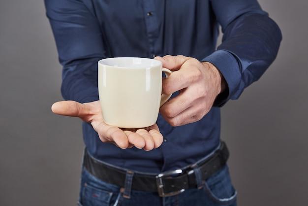 Hübscher bärtiger mann mit stilvollem haarbart und schnurrbart auf ernstem gesicht im hemd, das weiße tasse oder tasse hält, die tee oder kaffee im studio auf grauem hintergrund trinken.