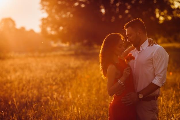 Hübscher bärtiger mann umarmt frau im roten kleiderangebot, das auf dem goldenen sommergebiet steht