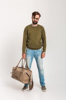 Hübscher bärtiger stilvoller mann, der lokal gekleidet im sweatshirt mit reisetasche aufwirft, jeans und sonnenbrille tragend