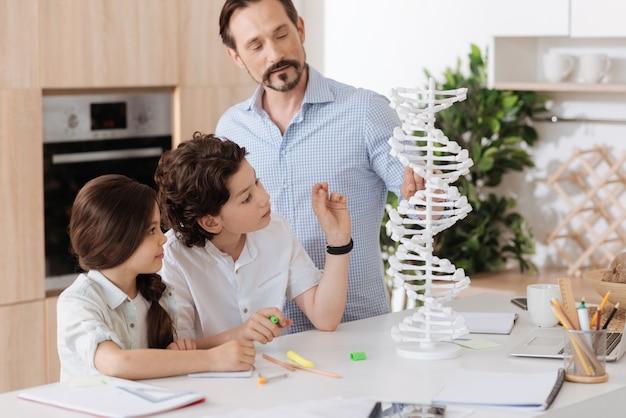Hübscher bärtiger vater, der die dna-struktur erklärt, indem er auf das 3d-modell zeigt, während seine kinder ihm aufmerksam zuhören