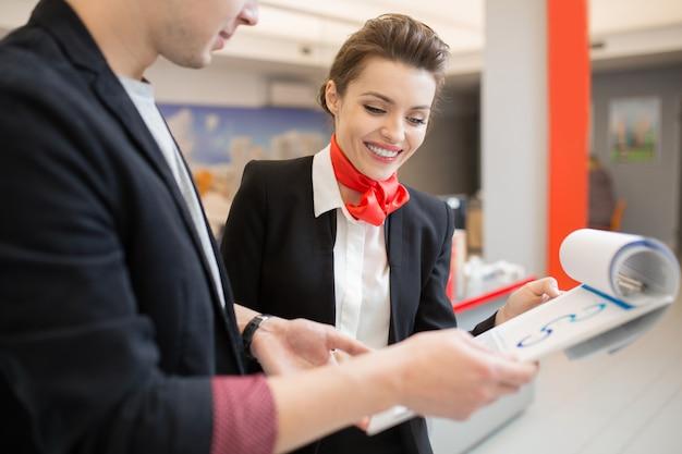 Hübscher bankmanager, der dem kunden den investitionsplan zeigt
