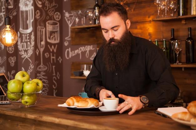 Hübscher barkeeper hinter einer bar mit einem zubereiteten kaffee. vintage-kneipe.