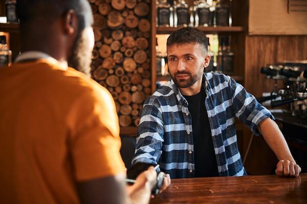 Hübscher barkeeper mit terminal für kontaktloses bezahlen