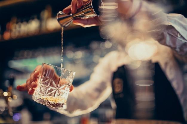 Hübscher barmixer, der das trinken und die cocktails an einem zähler macht