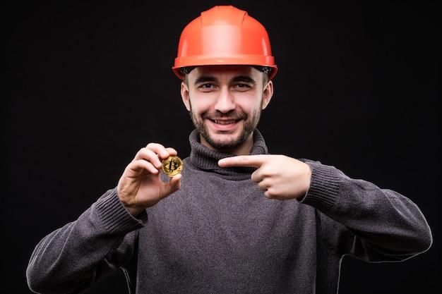 Hübscher bergmann des jungen mannes im schützenden hemlet zeigte auf bitcoin, das auf schwarz isoliert wurde