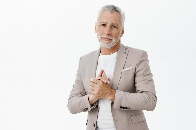 Hübscher berührter älterer mann im anzug, der etwas entzückendes ansieht