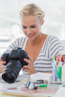 Hübscher bildeditor, der ihre digitalkamera betrachtet