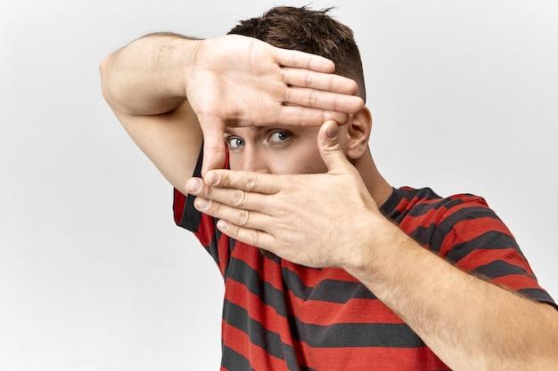Hübscher blauäugiger fotograf in stilvollem t-shirt, der mit seinen händen einen fotorahmen macht, sich auf die augen konzentriert und den schülern das fotografieren beibringt. menschen, lebensstil, spaß und körpersprache