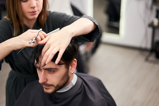 Hübscher blauäugiger mann, der im friseurladen sitzt. friseur friseur frau schneidet seine haare. friseurin.