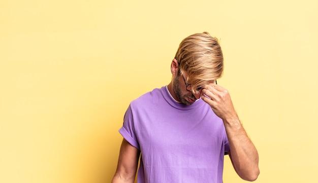 Hübscher blonder erwachsener mann, der sich gestresst, unglücklich und frustriert fühlt, die stirn berührt und unter migräne mit starken kopfschmerzen leidet