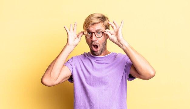 Hübscher blonder erwachsener mann, der sich schockiert, erstaunt und überrascht fühlt und eine brille mit erstauntem, ungläubigem blick hält
