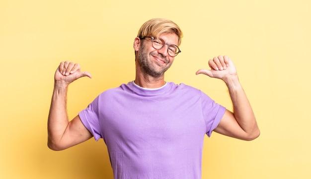 Hübscher blonder erwachsener mann, der traurig, enttäuscht oder wütend aussieht, daumen nach unten zeigt, wenn er nicht einverstanden ist und sich frustriert fühlt